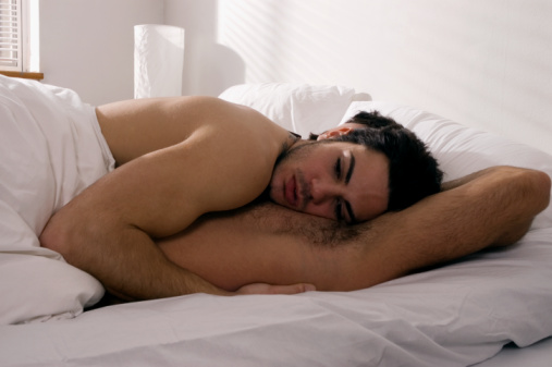 Gay man lying atop boyfriend in bed